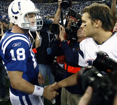 Indianapolis Colts quarterback Peyton Manning, left, and New England Patriots quarterback Tom Brady (12) meet at midfield after the Patriots beat the Colts, 24-20 at the RCA Dome on Sunday.